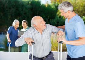 caregiver assisting an elderly man