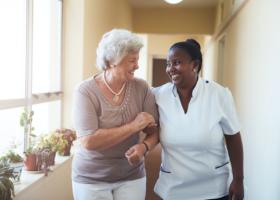 caregiver assisting elder woman in walking