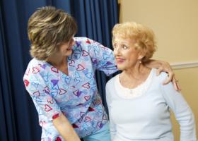 caregiver assisting an elder woman